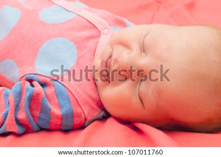Smiling Newborn Baby Sleeping on Pink Blanket