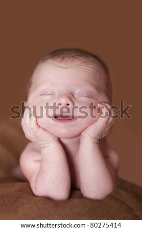 Smiling newborn baby with hands under chin. Looks like she is dreaming - stock photo