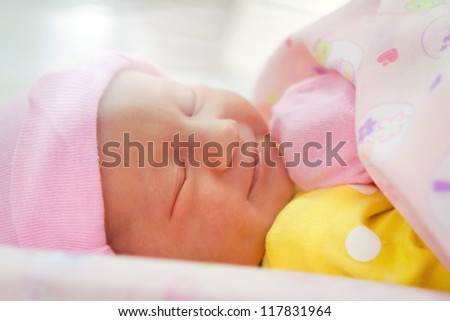 Smiling newborn girl sleeping close-up - stock photo