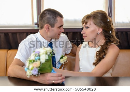 Smiling newlyweds sit at corner booth by windows while holding floral bridal bouquet