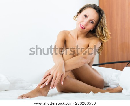 Smiling nude woman sitting in her bedroom on the bed