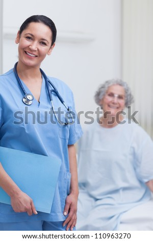 Smiling nurse holding a folder in hospital ward - stock photo