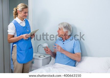 Smiling nurse holding digital tablet while interacting with senior man at hospital