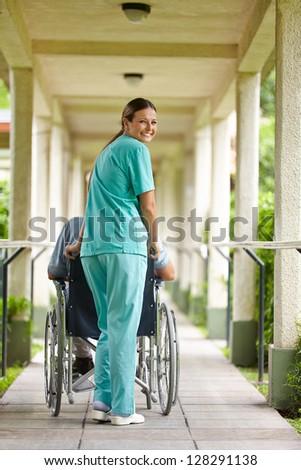 Smiling nurse pushing senior man in wheelchair in a nursing home - stock photo