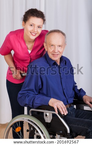 Smiling nurse standing by the disabled in a wheelchair