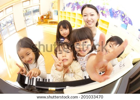 smiling nursery and children in front of the piano - stock photo