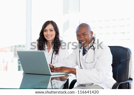 Smiling nurses seriously working while sitting at the desk in a bright room - stock photo