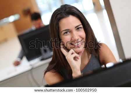 Smiling office worker at ther desk - stock photo