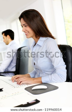 Smiling office worker in front of desktop computer - stock photo