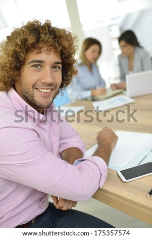 Smiling office-worker sitting at desk