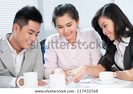 Smiling office workers being occupied with paperwork indicating positive business results - stock photo