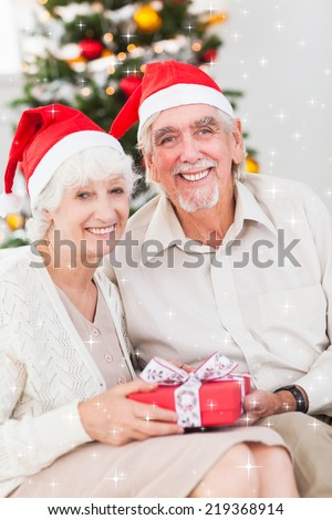 Smiling old couple swapping christmas gifts against twinkling stars - stock photo