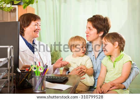 Smiling old female pediatrician doctor examining two kids in clinic