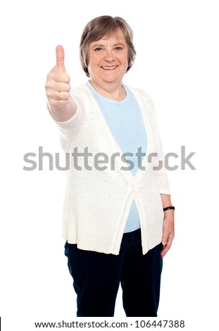 Smiling old lady showing thumbs up gesture to camera. Isolated on white - stock photo