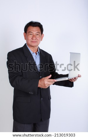 Smiling old man businessman working with laptop. Isolated over white background