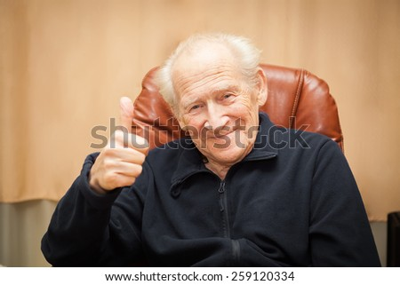 smiling old man sitting in a chair showing thumbs up - stock photo