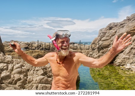 Smiling old man talks after snorkelling. Shot on the Otter trail in the Tsitsikamma National Park, Garden Route area, Western Cape, South Africa.  - stock photo