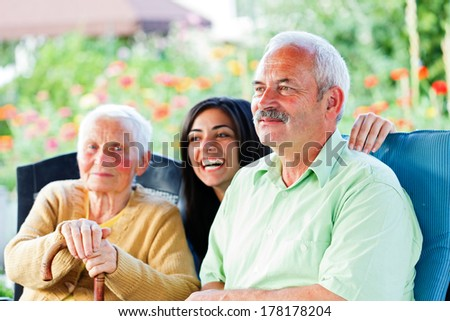Smiling old man visiting her elderly  mother. - stock photo