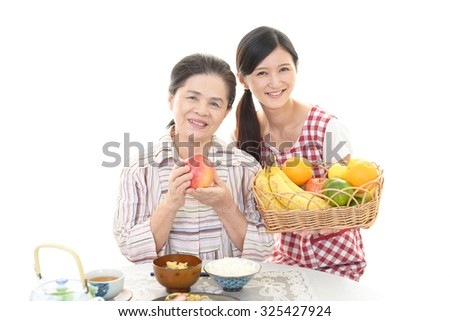 Smiling old woman and young lady - stock photo