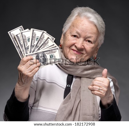 Smiling old woman holding money in hands - stock photo