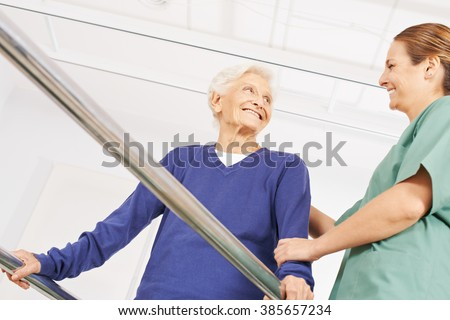 Smiling old woman in physiotherapy on a treadmill with physiotherapist - stock photo