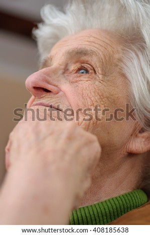 Smiling old woman looking up - stock photo