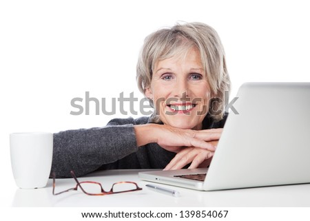 Smiling old woman resting on the table with laptop and cup of coffee