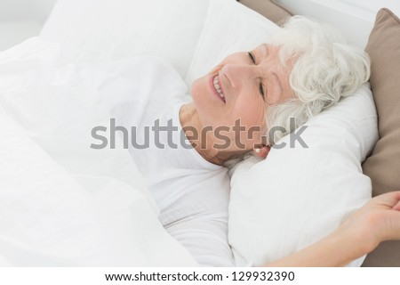 Smiling old woman sleeping on the bed