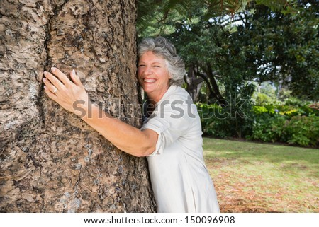 Smiling older woman hugging a tree in a park - stock photo