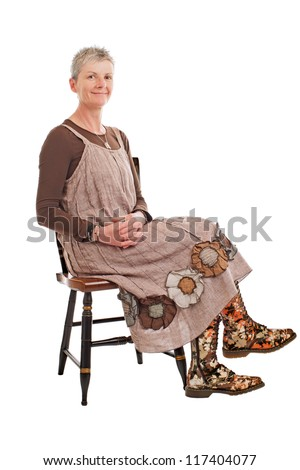 Smiling older woman with short gray hair sits sideways on chair, hands clasped. She wears flowered boots and brown cotton shift dress. Isolated on white background, vertical, copy space.