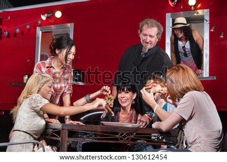 Smiling outdoor mobile restaurant chef with happy patrons - stock photo