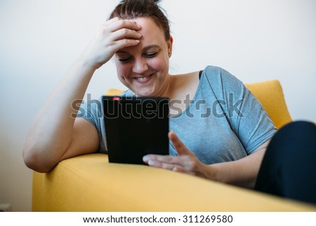 Smiling overweight woman reading a book on sofa - stock photo