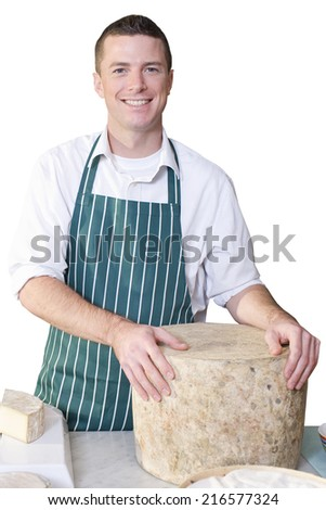 Smiling owner standing near large wheel of cheese - stock photo