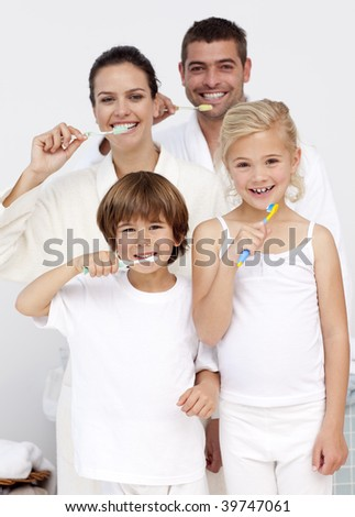 Smiling parents and children cleaning their teeth in bathroom - stock photo