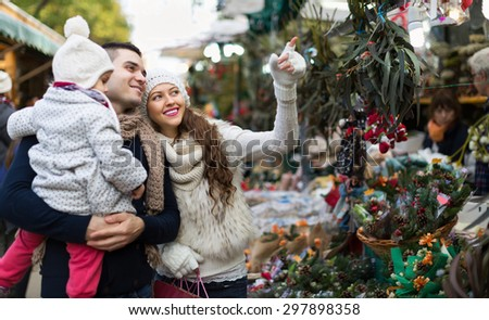Smiling parents and little child buying red Euphorbia at Christmas fair. Focus on woman