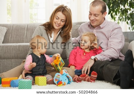 Smiling parents and small daughter looking at baby sitting on floor.