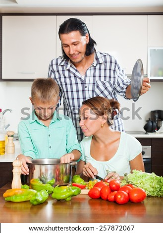 Smiling parents and teenager cooking together at home kitchen