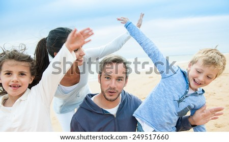 smiling parents and their two children, a beautiful family is posing with their arms up like planes at the beach. - stock photo