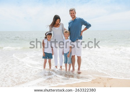 Smiling parents and their two children posing with their feet in the waves - stock photo
