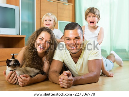 Smiling parents and two daughters lying on the floor at home with Siamese. Focus on man  - stock photo