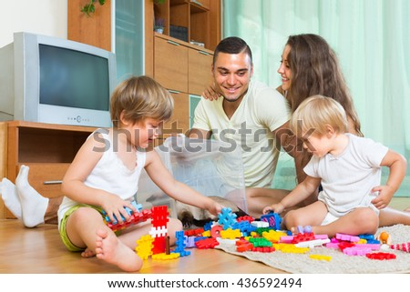 Smiling parents and two little daughters playing at home. Focus on man