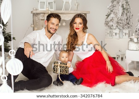 Smiling parents giving Christmas present to son - stock photo