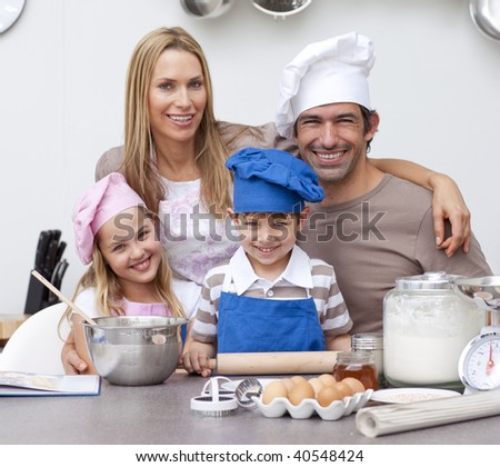 Smiling parents helping children baking cookies in the kitchen