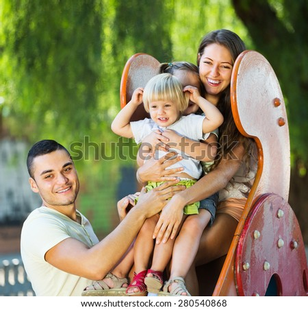 Smiling parents helping small kids on slide in summer day - stock photo