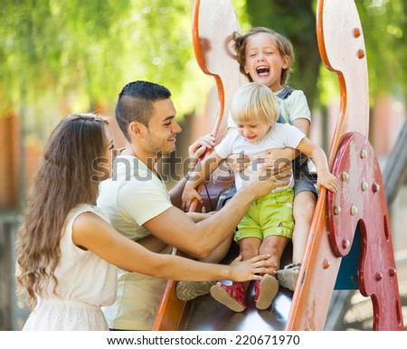 Smiling parents helping two kids on slide in summer day - stock photo