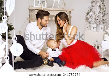 Smiling parents looking each other in Christmas scenery  - stock photo