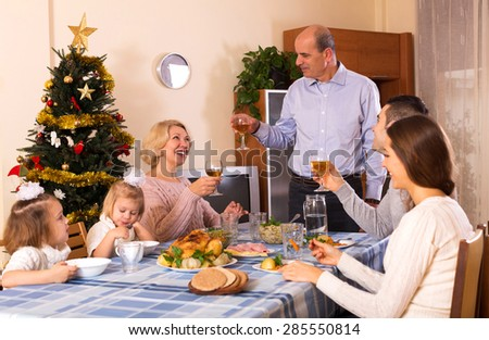 smiling parents with adult kids and grandchildren celebrating cristmas
