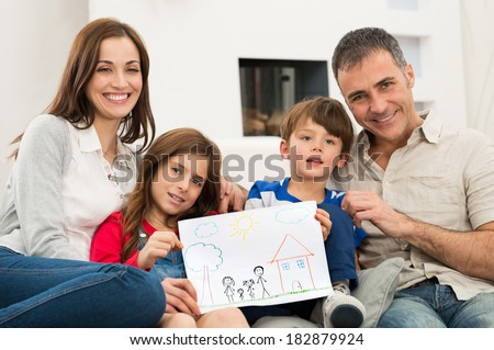 Smiling Parents With Children Sitting On Couch Showing Together Drawing of a new Home - stock photo