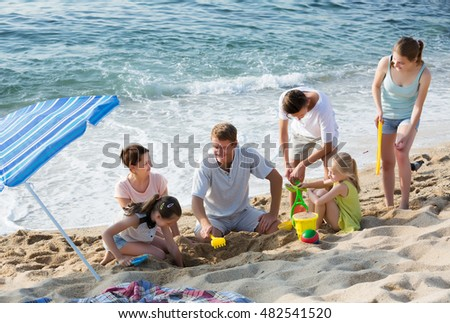 Smiling parents with four children in different ages playing with beach toys on sunny summer day