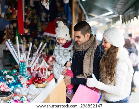 Smiling parents with small daughter at counter of X-mas market
